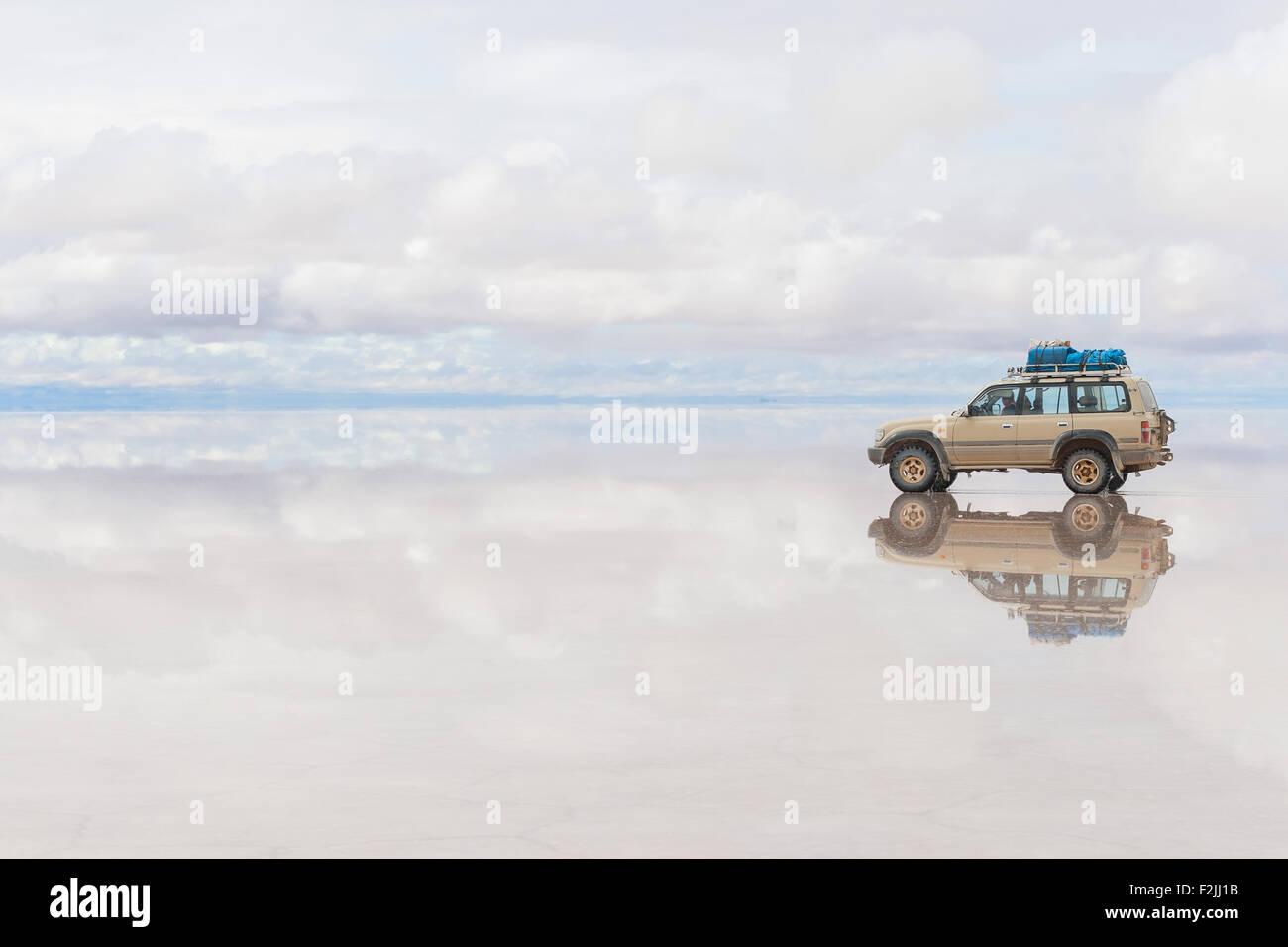 Offroad-Fahrzeug auf die reflektierte Oberfläche des Sees Salar de Uyuni in Bolivien Stockfoto