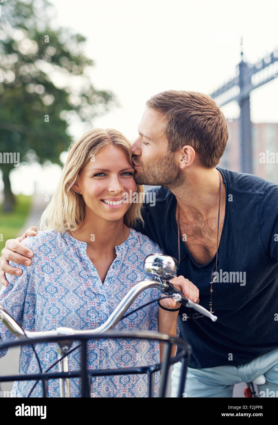 Liebevoller junger Mann seine Freundin auf der Stirn küssen, wie sie einen Sommertag an der frischen Luft auf Stockbild