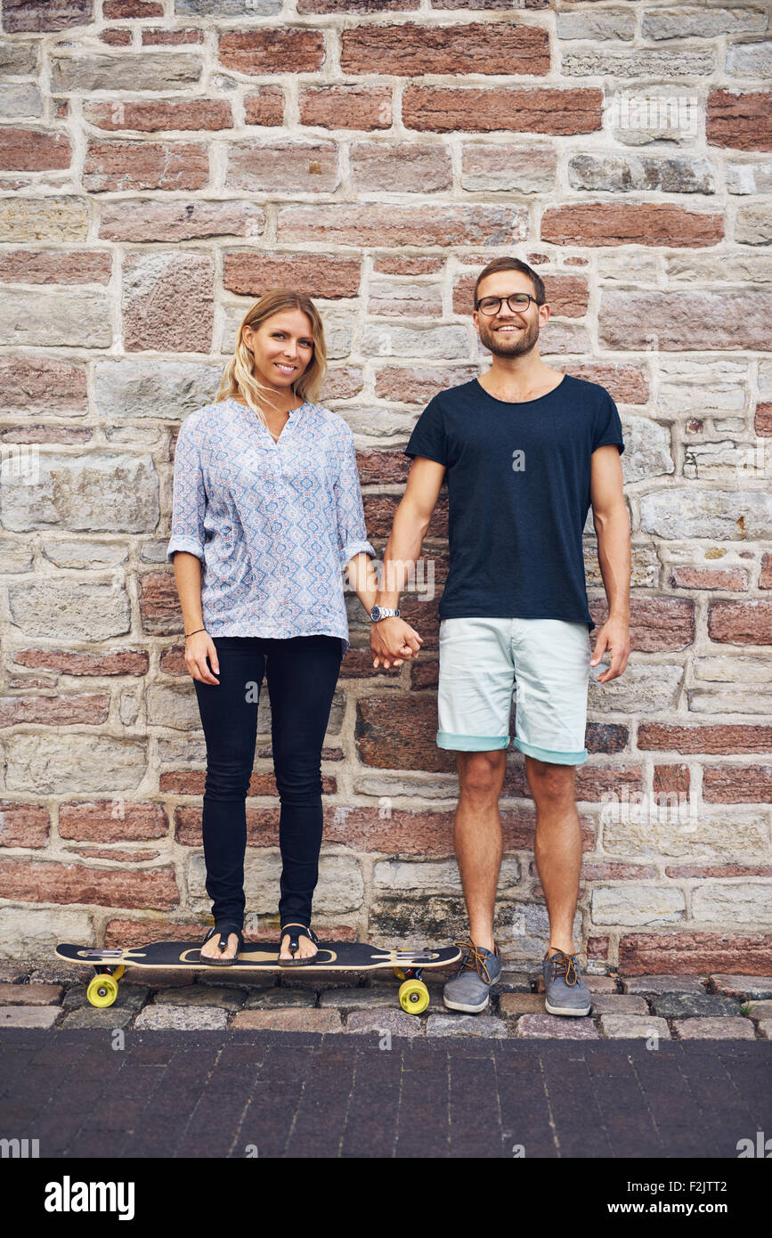 Junges Paar haltende Hand Wand gelehnt Stockbild