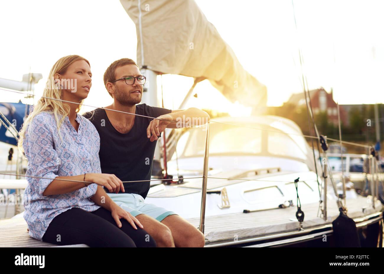 Süße junge Liebhaber sitzen vor einer Yacht und Blick in die Ferne während des Sonnenuntergangs. Stockbild