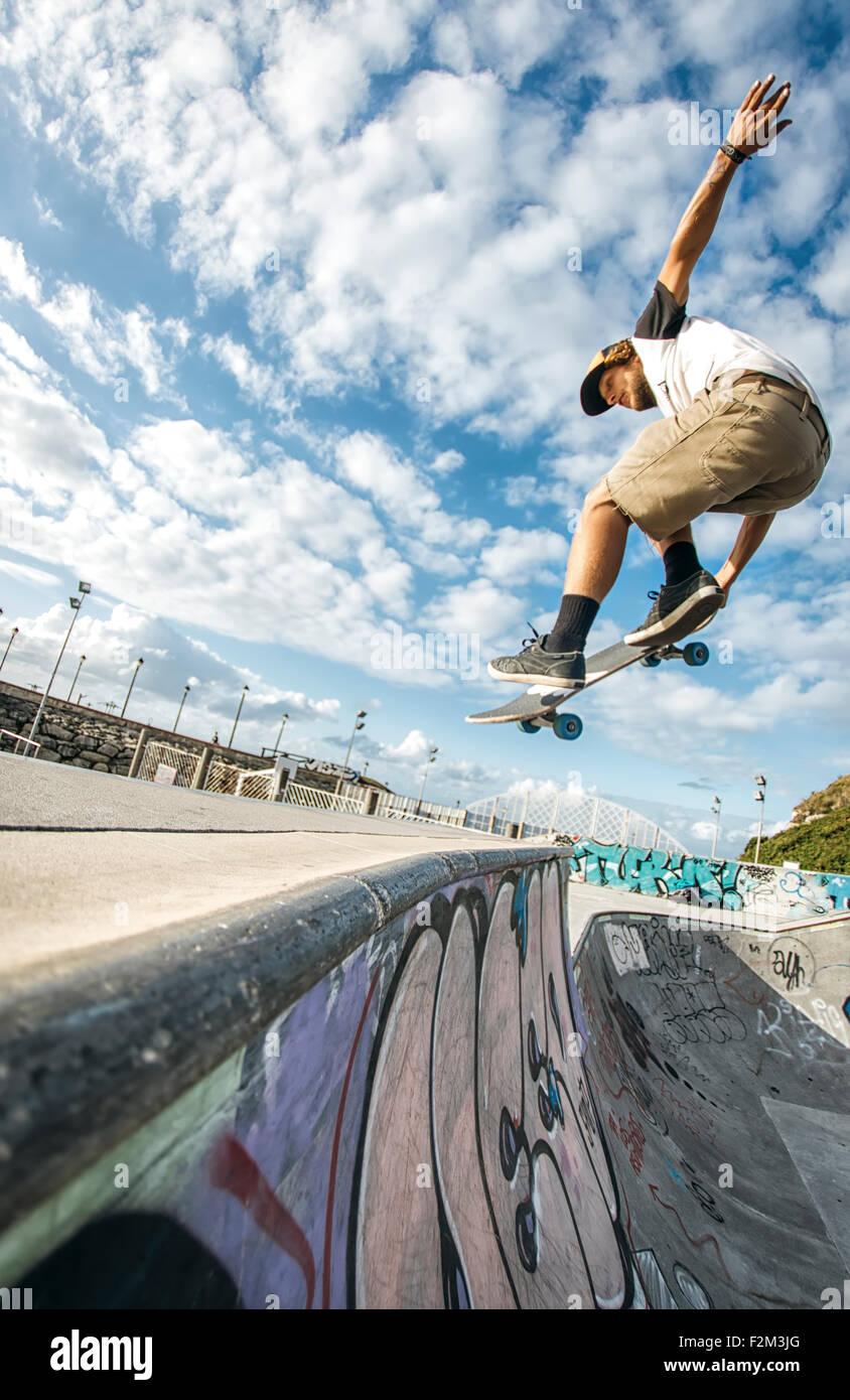 Junge Skater springen in der Luft in einem skatepark Stockbild