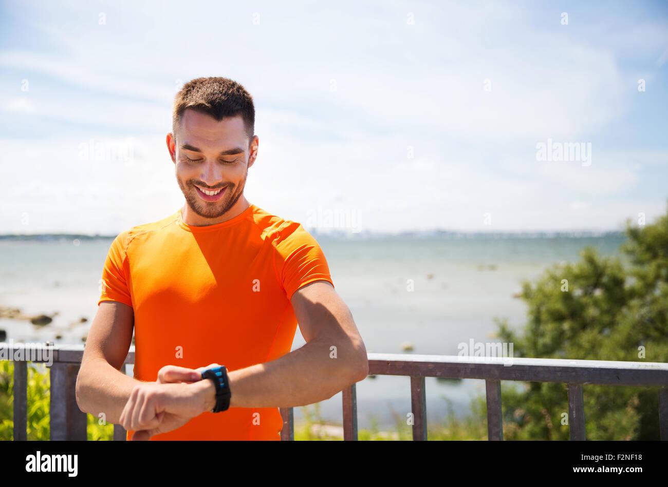 lächelnder junge Mann mit intelligenten Armbanduhr am Meer Stockbild