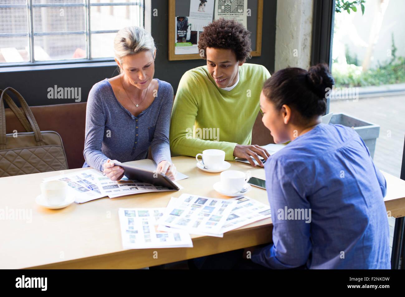 Geschäftsleute, die mit digital-Tablette im Büro treffen Stockfoto