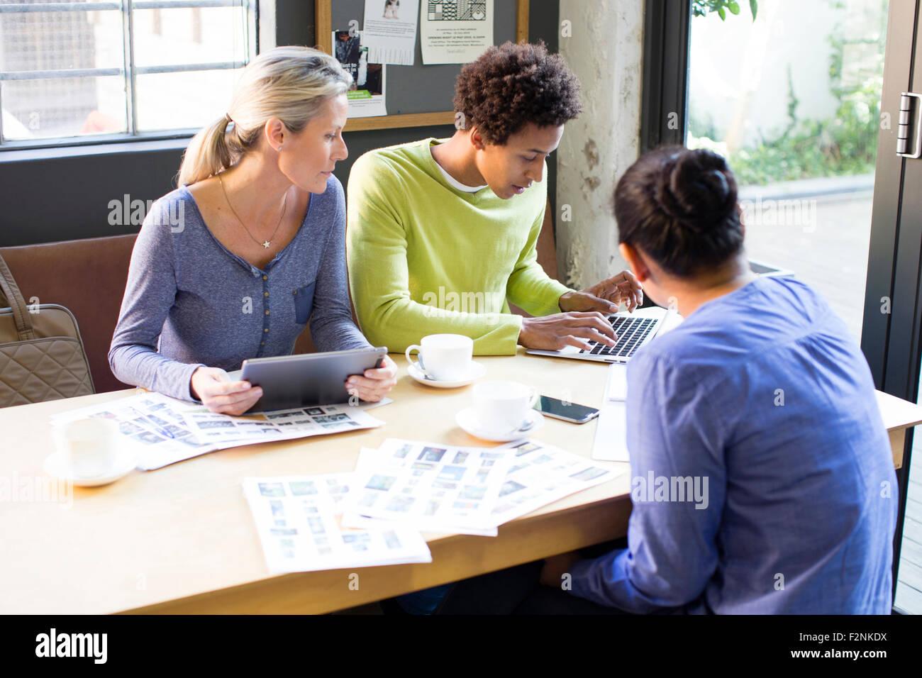Geschäftsleute, die mit Technologie im Büro treffen Stockfoto