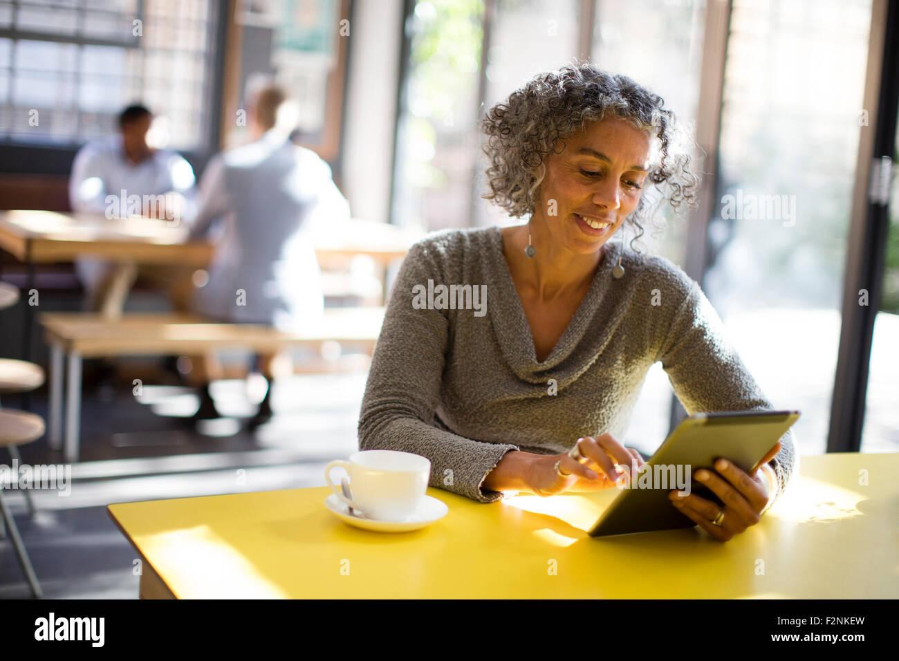 Ältere Frau mit digital-Tablette im café Stockfoto
