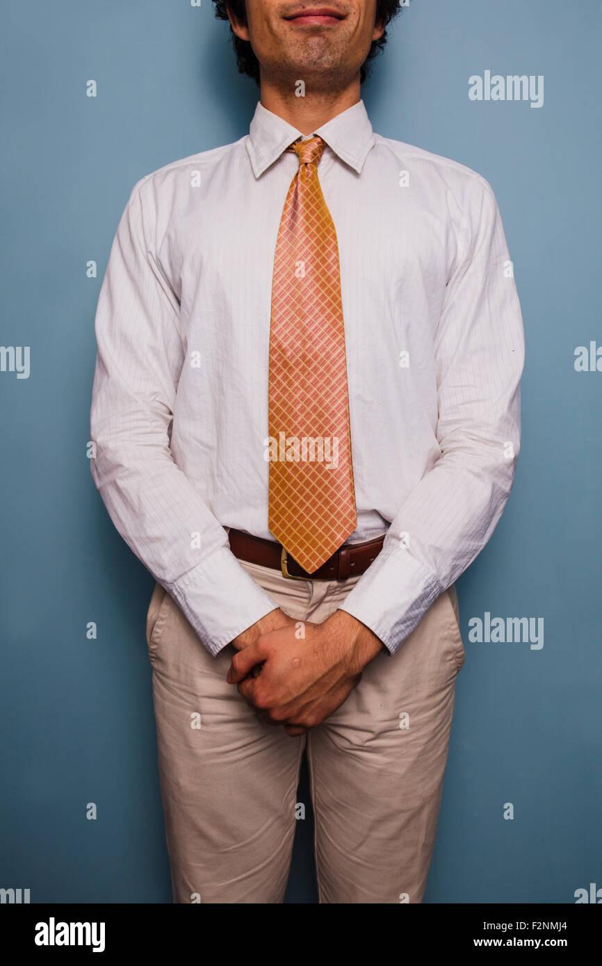 Junger Mann stehend mit einer blauen Wand, er trägt eine Krawatte Stockbild