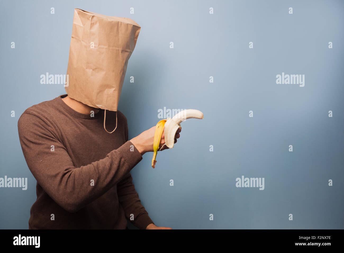 ein junger Mann mit einer Papiertüte auf dem Kopf zeigt eine Banane, als wäre es eine Waffe! Stockbild