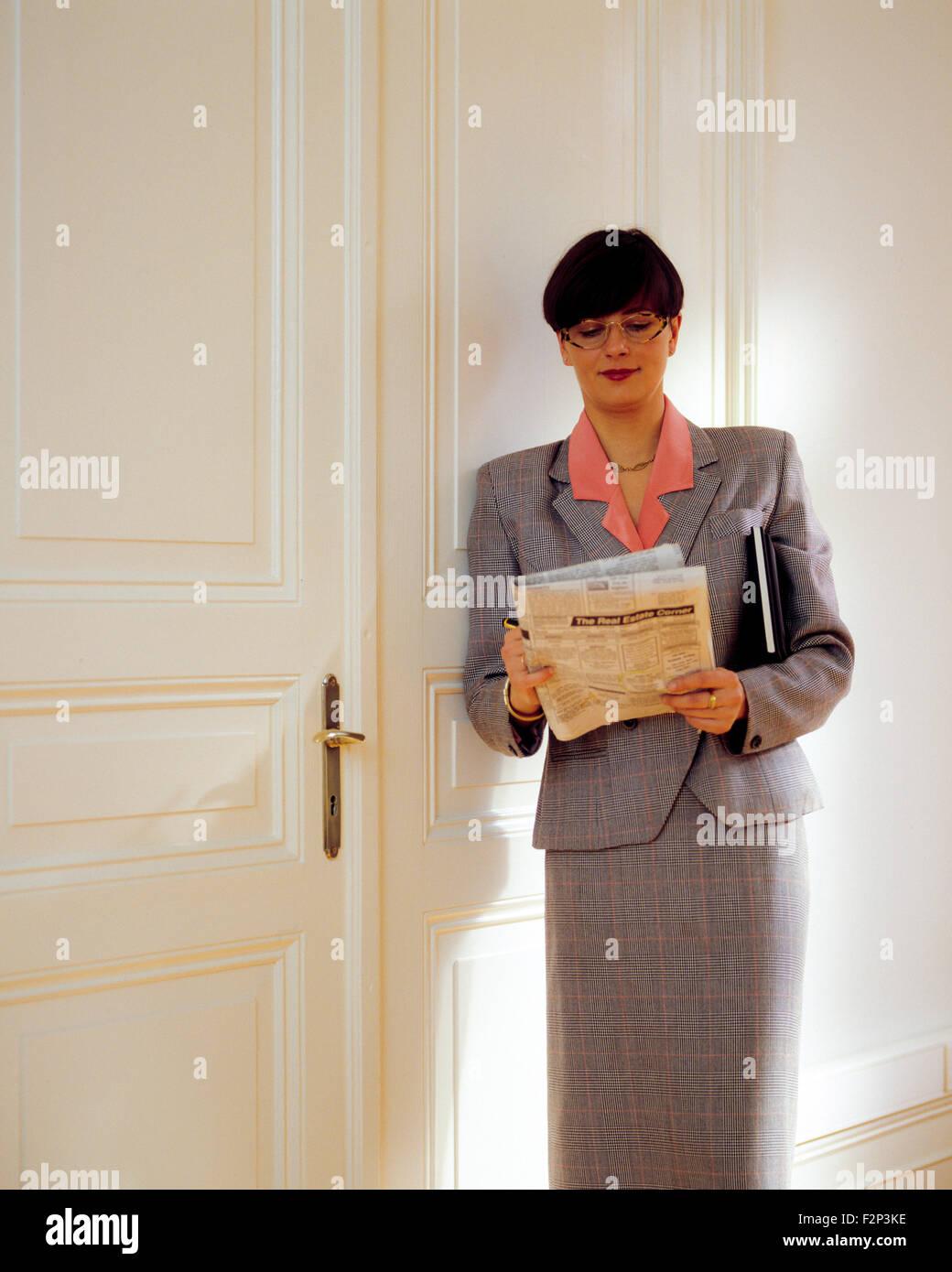 Real Estate Agent lesen Kleinanzeigen im Büro Stockbild