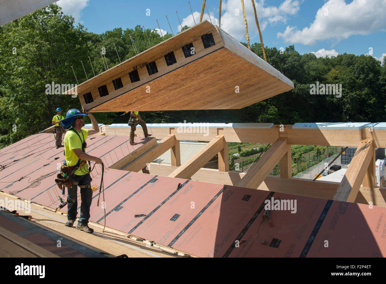 Bauarbeiter installieren Dachplatten auf Leed Platin Common Ground High School Gebäude. Stockbild