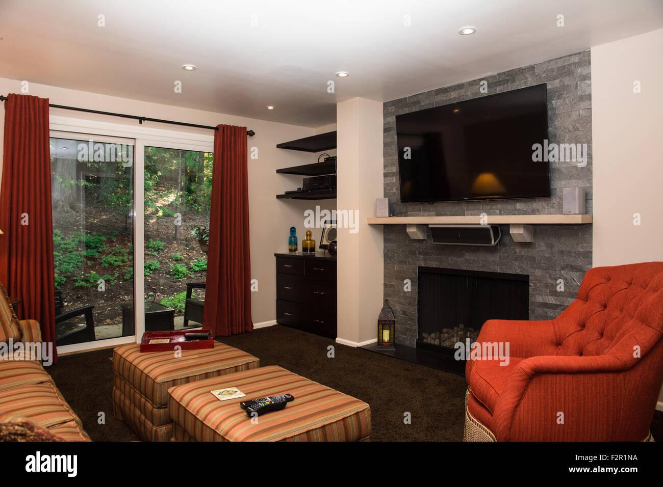 Ein Gemütliches Familienzimmer (Wohnzimmer) Mit Einem Kamin Und Einem  Großen Flachen TV (Fernsehen).
