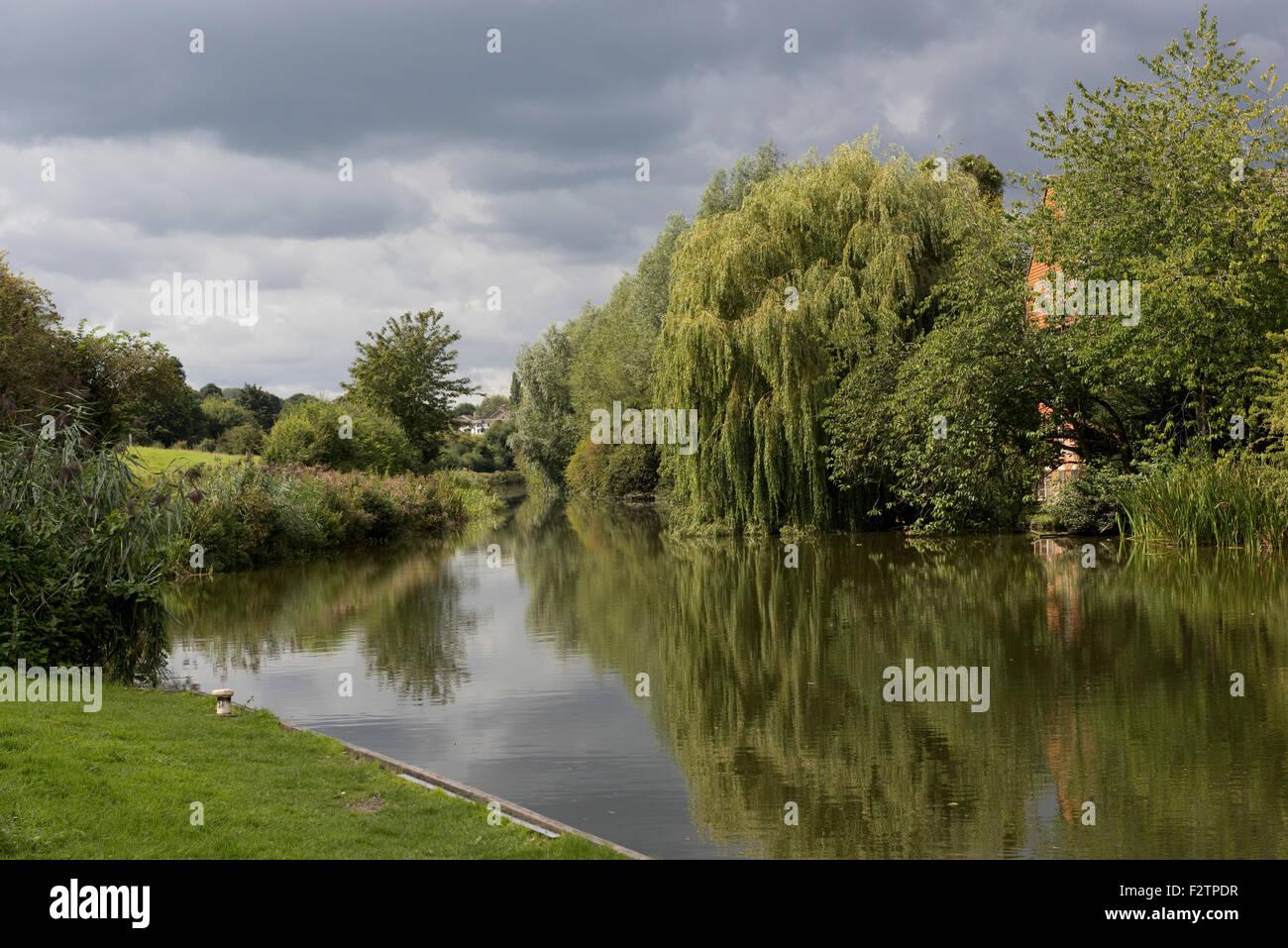 Reflexionen im Satill Wasser des Kennet und Avon Kanal am Portdown in der Nähe von Hungerford an einem Spätsommertag, Stockbild