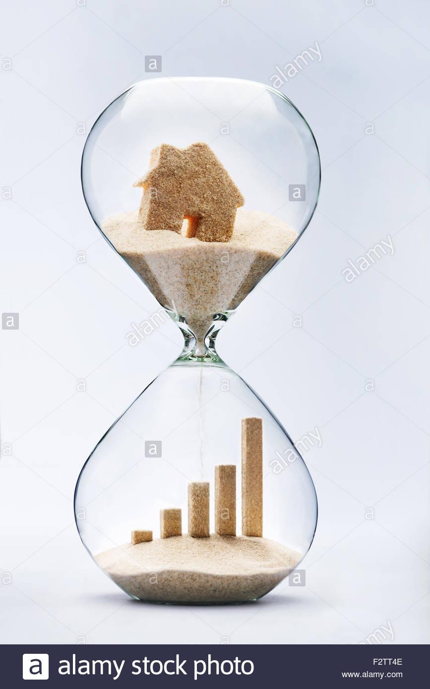 Immobilien-Konzept. Geschäft Wachstum Grafik gemacht aus sinkenden Sand Haus fließt durch Sanduhr Stockbild