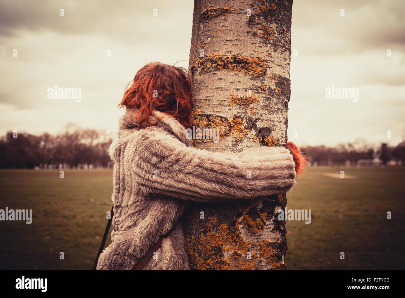 Junge Frau im Park an einem Wintertag und umarmt einen Baum Stockbild