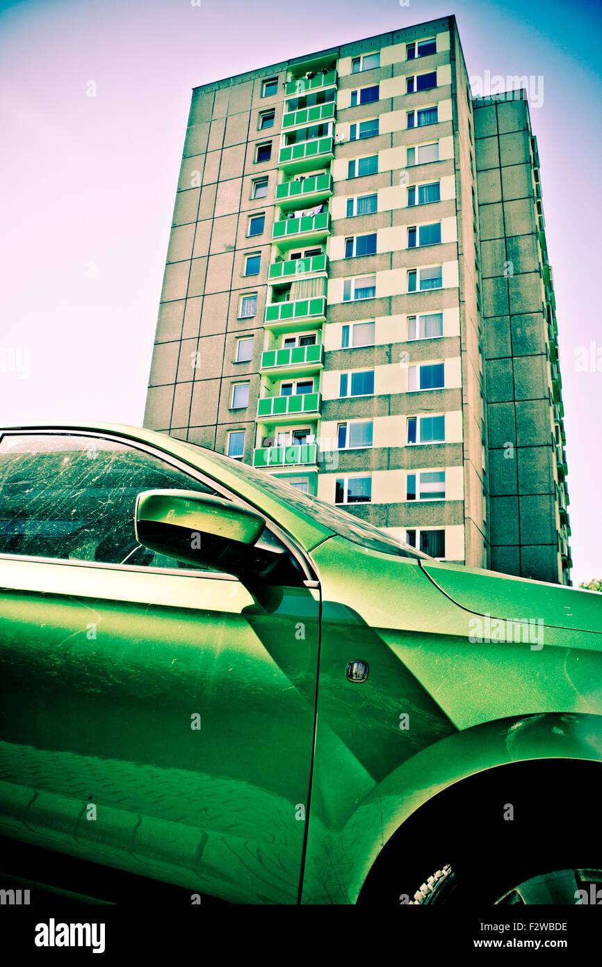grünes Auto vor einer Multi-Geschichte-Mehrfamilienhaus Stockbild