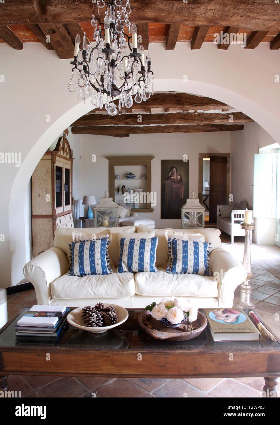 Kronleuchter und weißen Sofa mit blau gestreiften Kissen in einem ...