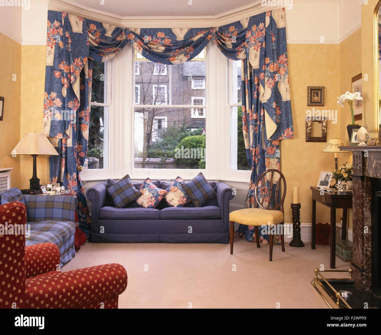 Gemusterte Swagged + Tailed Vorhänge An Erker Oben Blau Gelb Der Neunziger  Jahre Wohnzimmer Sofa