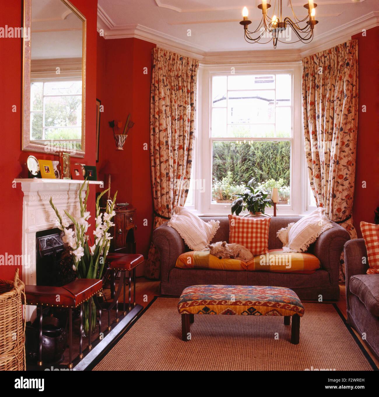Gepolsterte hocker und grauen sofa vor fenster mit floral for Sofa vor fenster