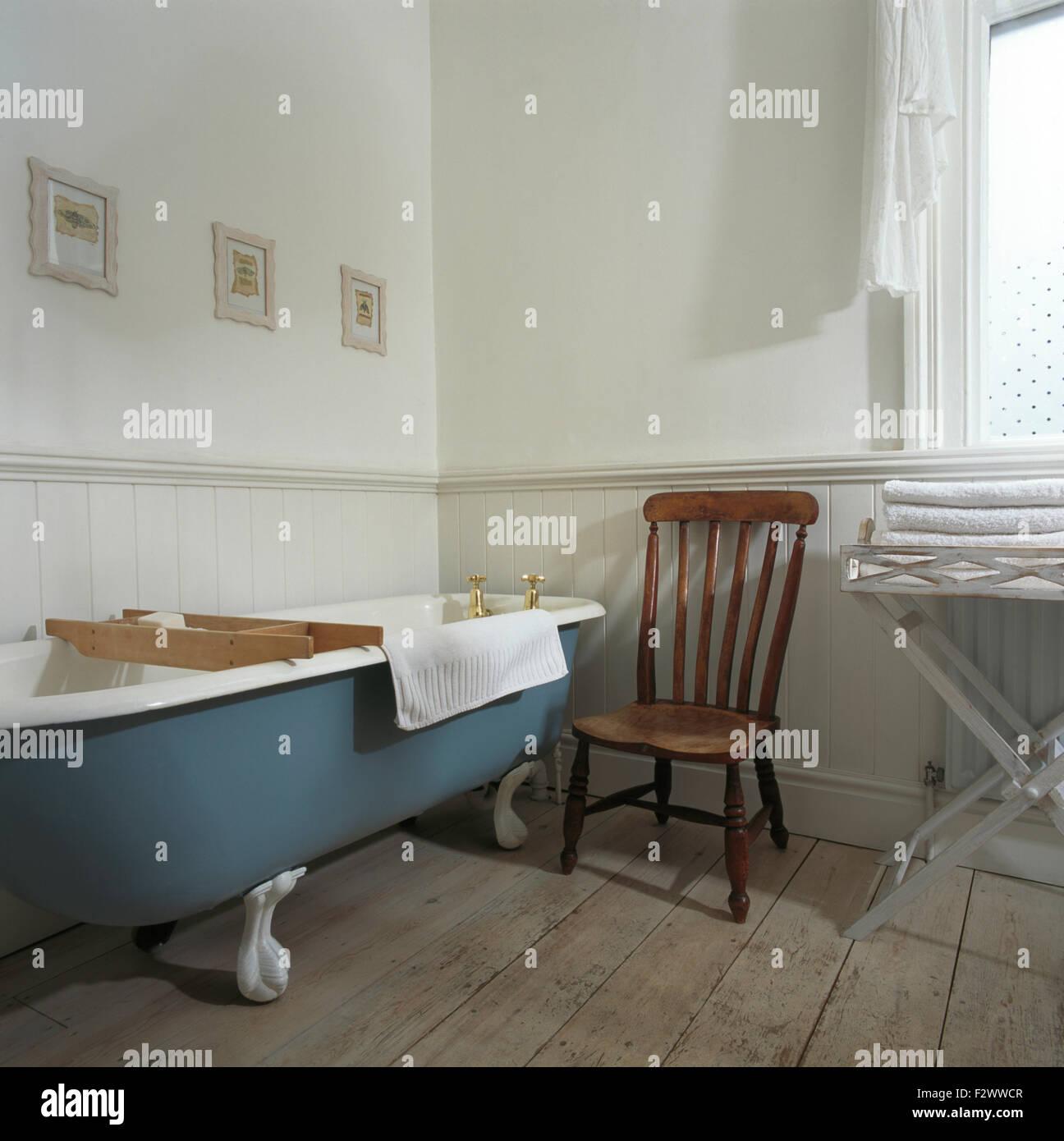 Antiker Holzstuhl neben blau Roll Top Bad im traditionellen ...