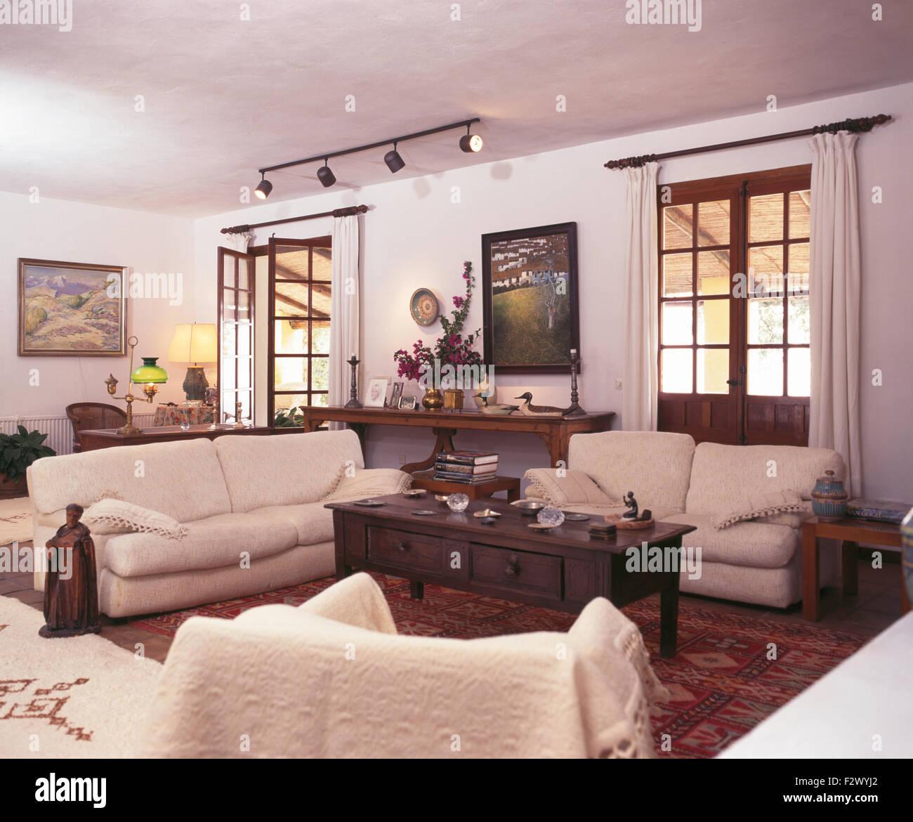 Cremefarbene Sofas Und Dunkles Holz Couchtisch In Weißen Spanischen  Wohnzimmer