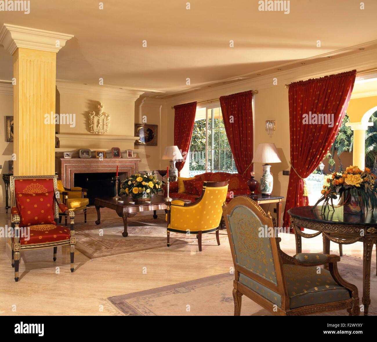 Im spanischen Wohnzimmer Sofa, rote Vorhänge und bunte Stühle ...