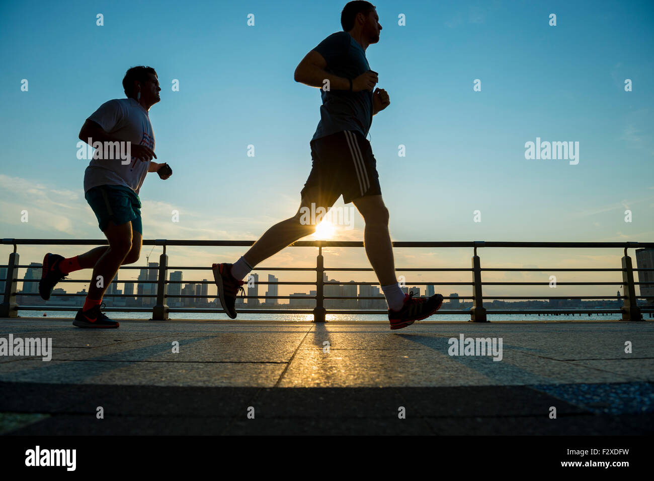NEW YORK CITY, USA - 15. August 2015: Silhouetten der Männer laufen bei Sonnenuntergang auf der Promenade des Stockbild
