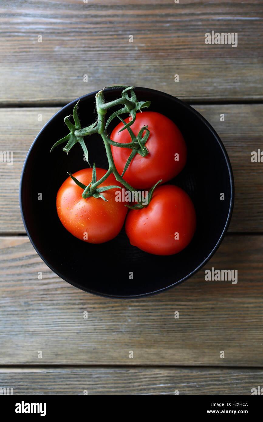 rote Tomaten in schwarz Schüssel, Ansicht von oben Stockbild
