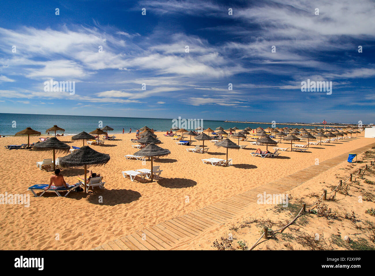 Algarve Strand Portugal mit Stroh Sonnenschirme Sonnenschirme. Stockbild