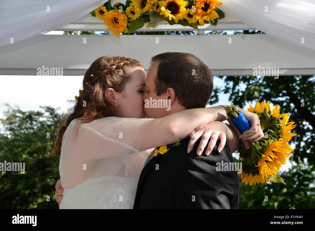 Mann und Frau haben einen leidenschaftlichen Kuss bei ihrer Hochzeit Stockbild