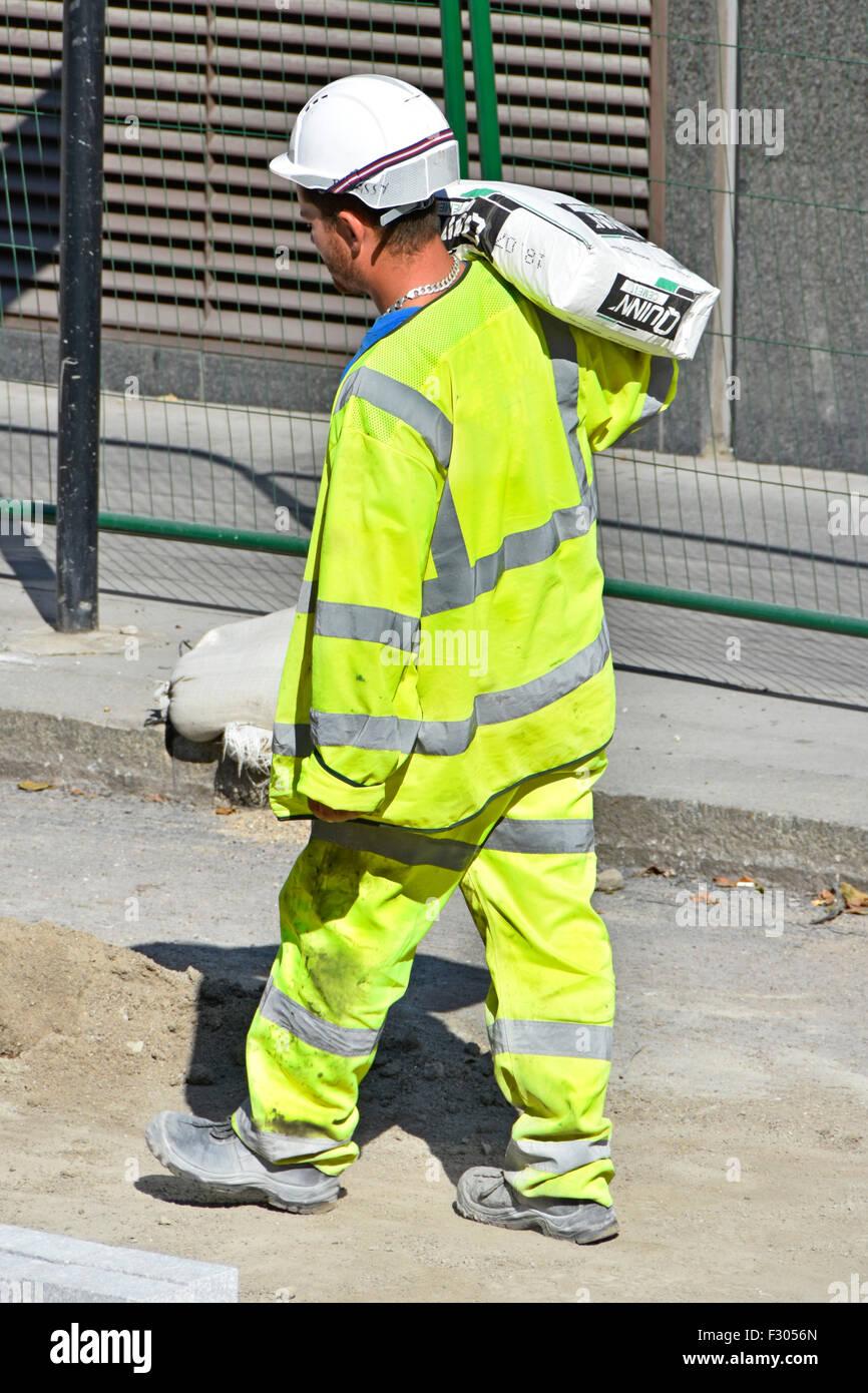 arbeiter die ein sack zement auf seiner schulter tragen hohe sichtbarkeit health safety