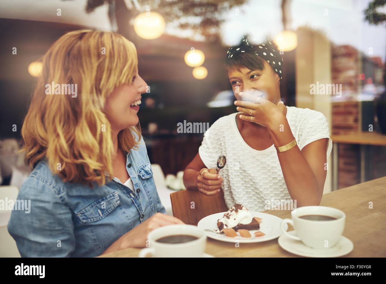 Zwei gute Freundinnen, die bei einer Tasse Kaffee zusammen in einem Kaffeehaus mit einem Lachen als die anderen Stockbild