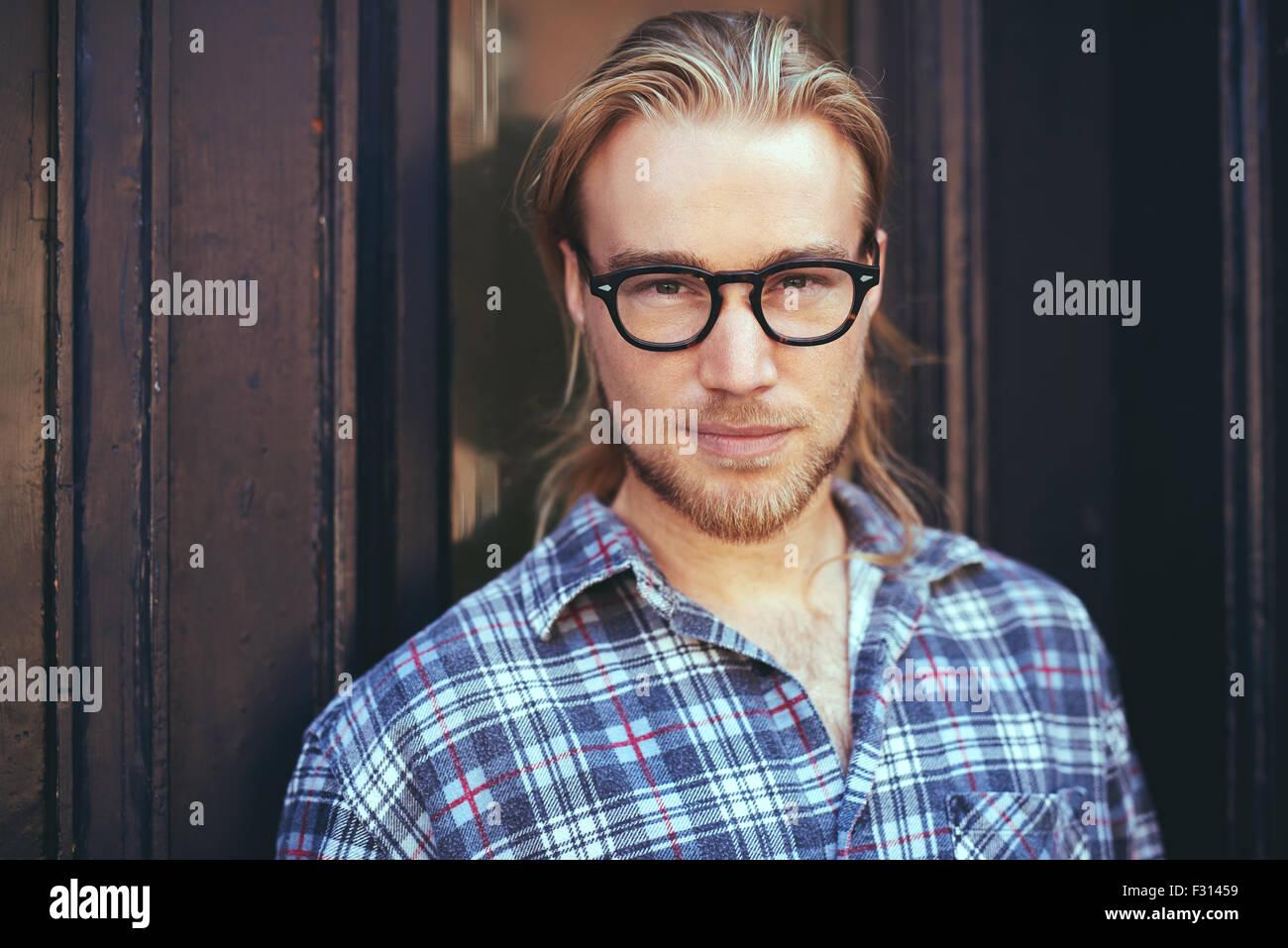 Closeup Portrait blonder Mann mit langen Haaren und Brille. Nachdenklicher Mann Stockbild