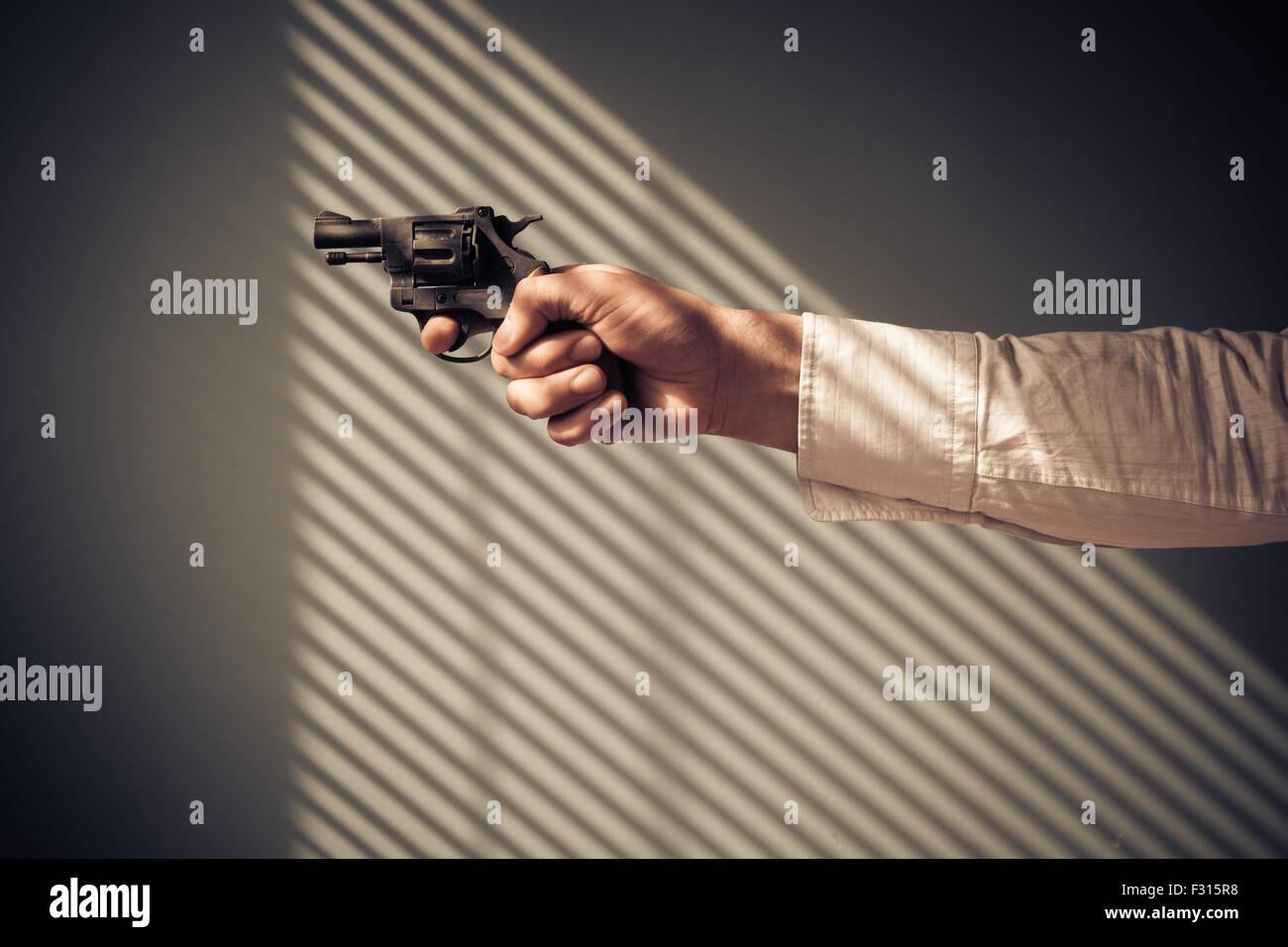 Mann zeigt einen Revolver an einem Fenster mit Schatten von den blinds Stockbild