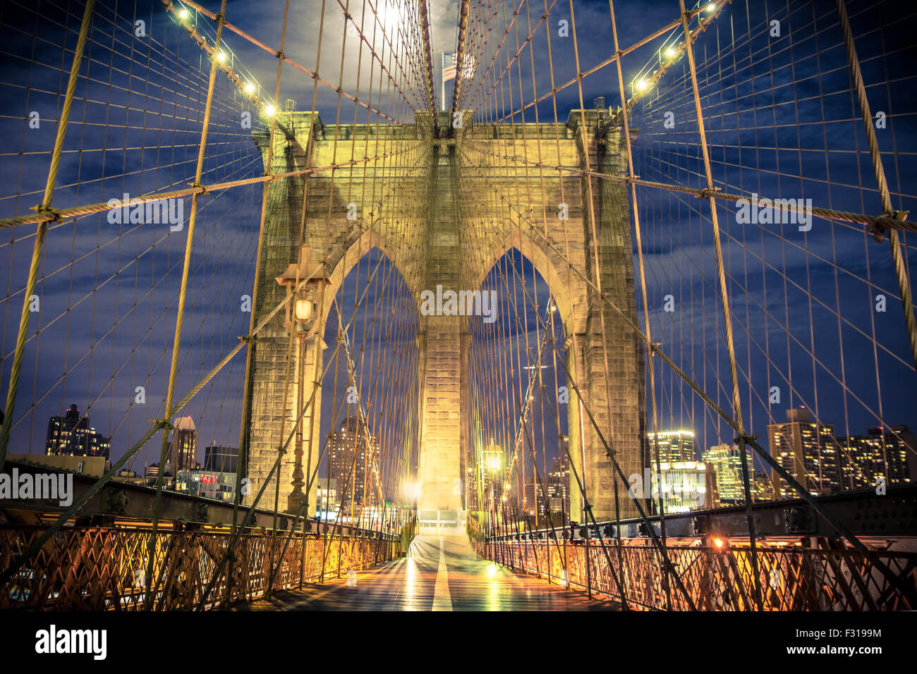 Blick auf historischen Brooklyn Bridge bei Nacht gesehen von der Fußgängerzone Stockbild