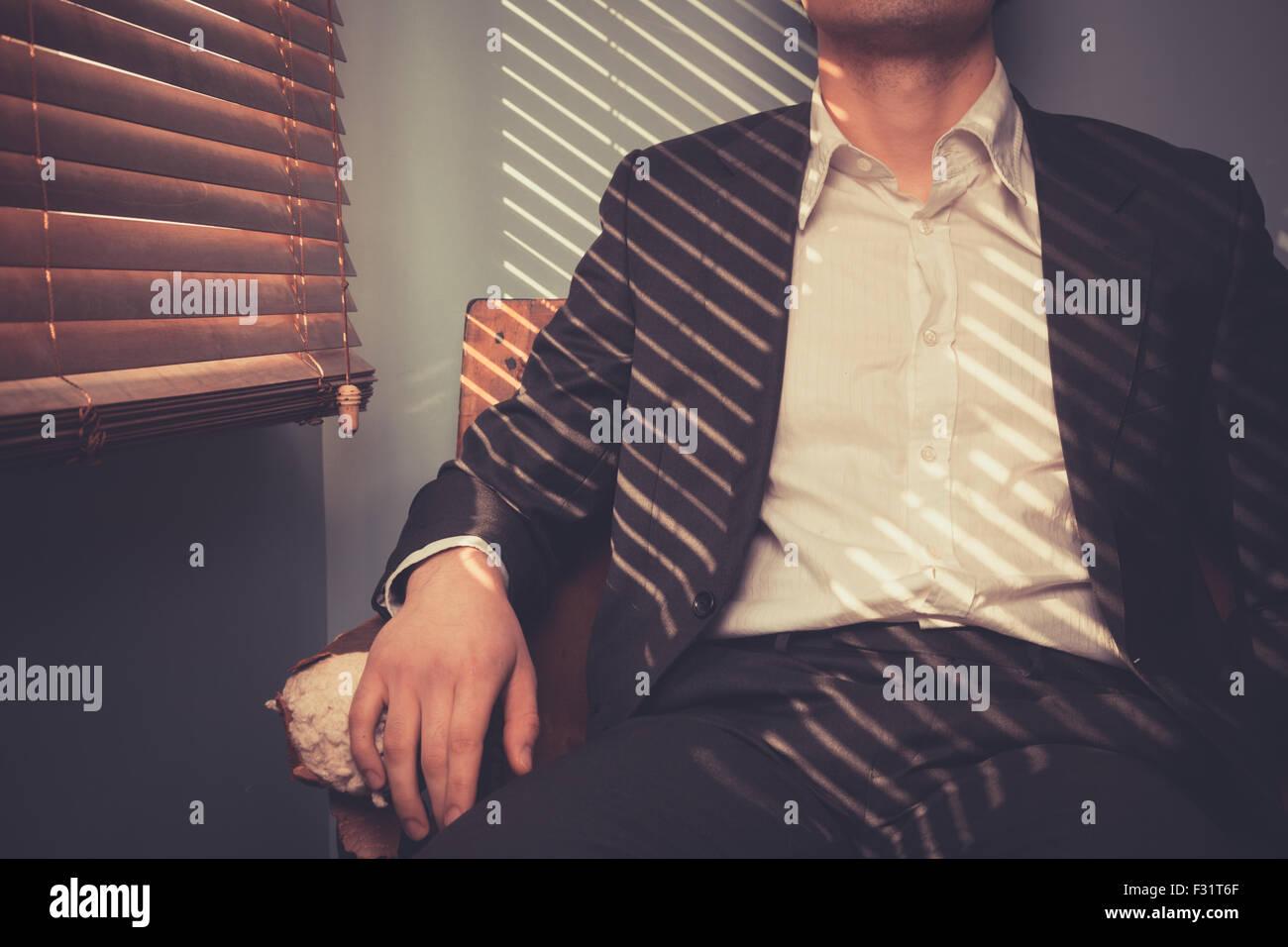 Junger Mann ist an einem sonnigen Tag entspannen Sie sich auf ein altes Sofa am Fenster Stockbild