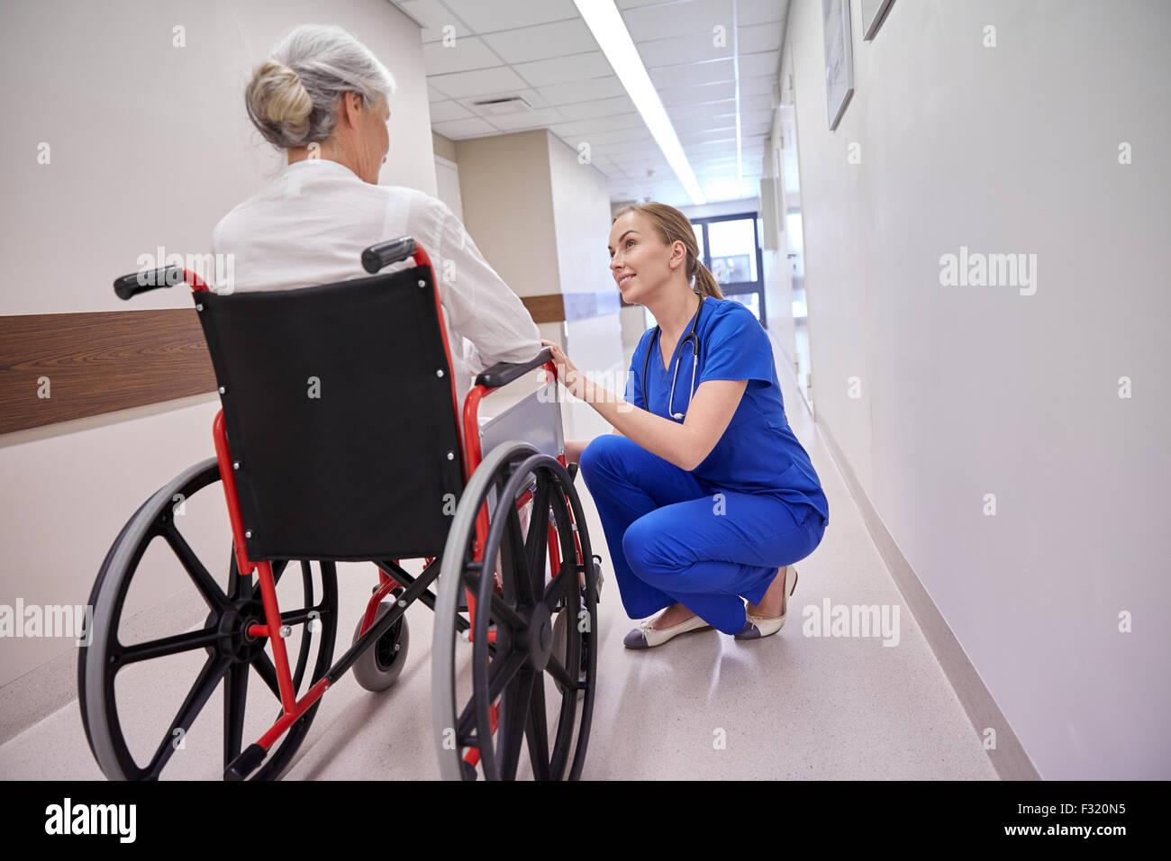 Krankenschwester mit senior Frau im Rollstuhl am Krankenhaus Stockbild