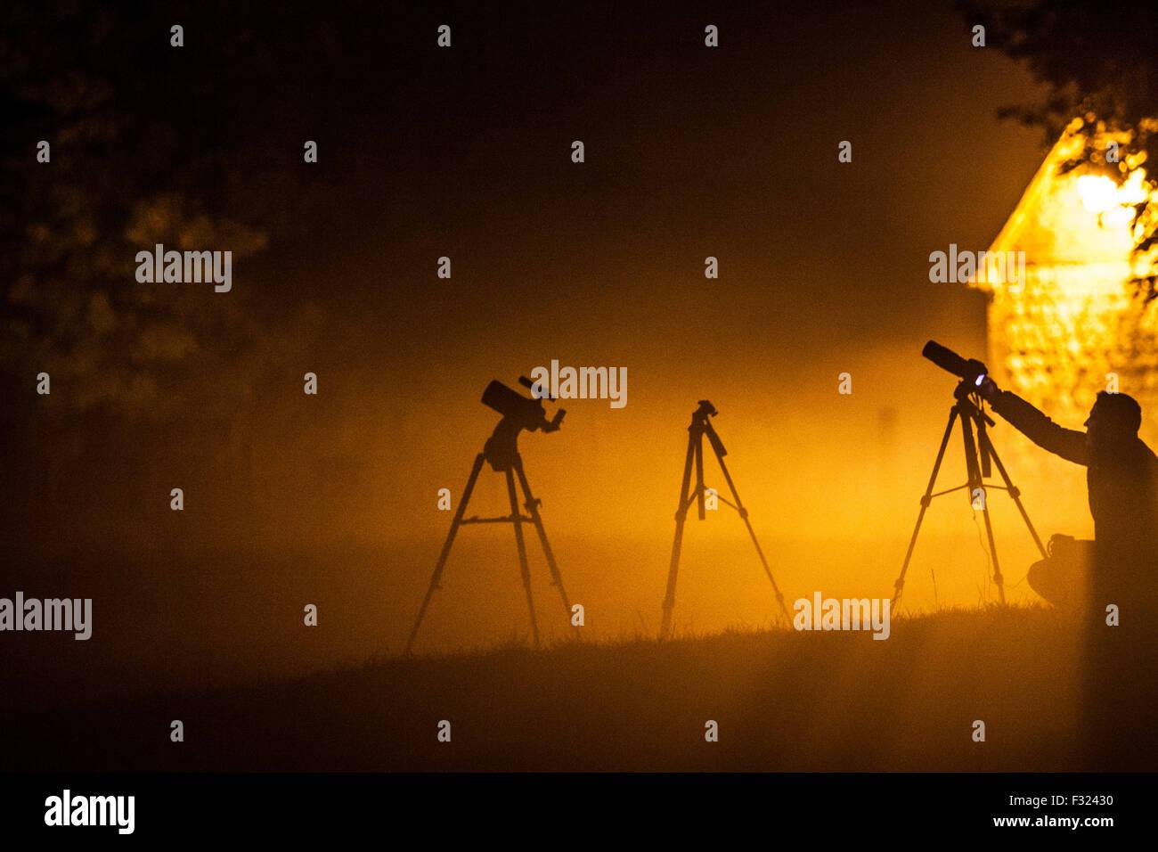 Silhouetten von Fotografen und Stative, die darauf warten, den Blutmond über Avebury zu fotografieren. Stockbild