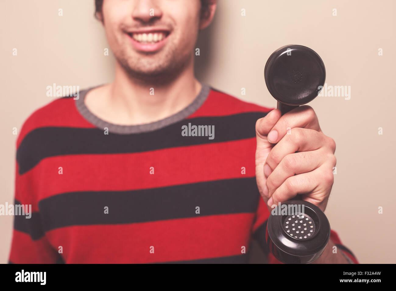 Ein glücklicher junger Mann hält einen Telefonhörer Stockbild