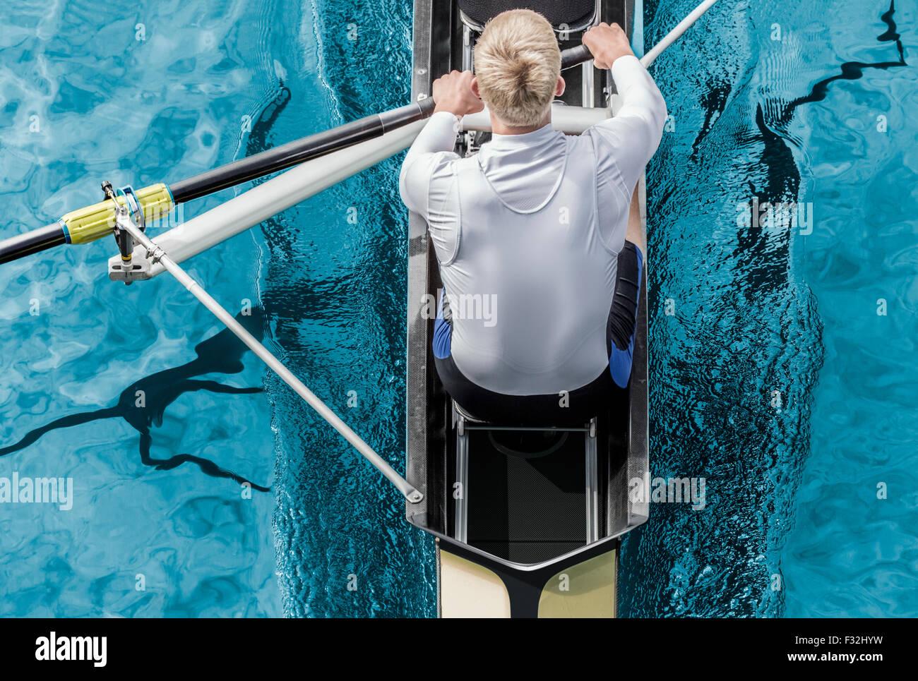 Draufsicht der sportlichen Wettkampf Ruderer, wer sein Paddel durch metallische blauen Wasser streichelt. Stockbild