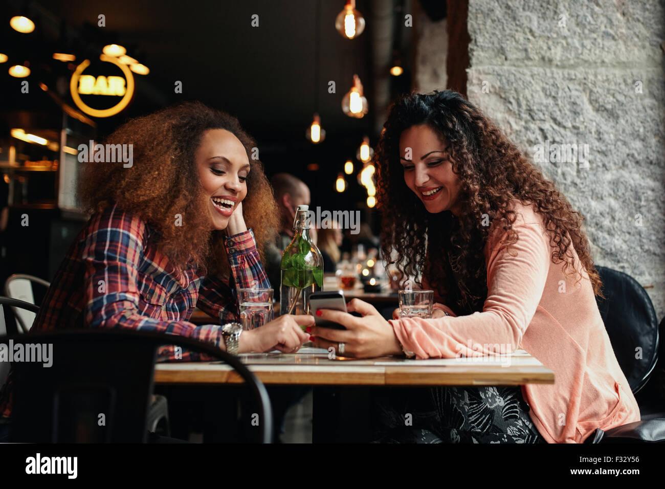 Junge Frauen im Café sitzen und Telefon benutzen. Freunde sitzen in einem Restaurant mit einer Frau zeigt ihr Stockbild