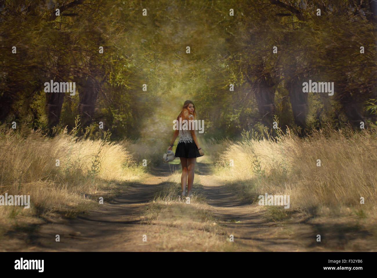 Großes Mädchen zu Fuß Trouhgt den Wald im Rückblick Stockbild