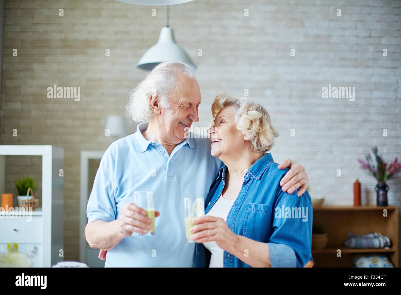 Ältere Mann und Frau halten Gläser mit gesunde hausgemachte Fruchtsaftgetränk und schauen einander Stockbild