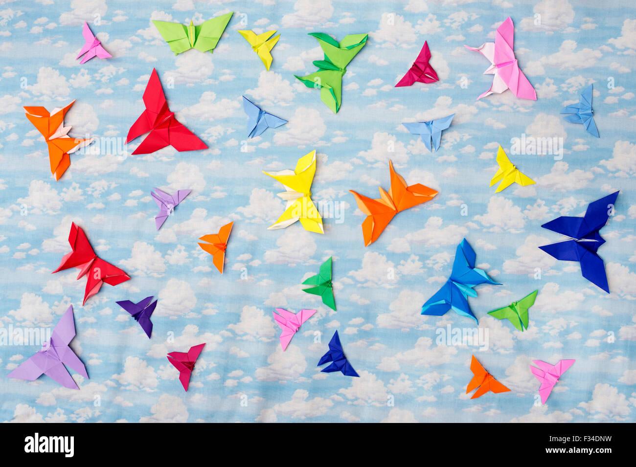 Bunte Origami Papier Schmetterlinge auf einem bewölkten Himmel Muster Hintergrund Stockbild