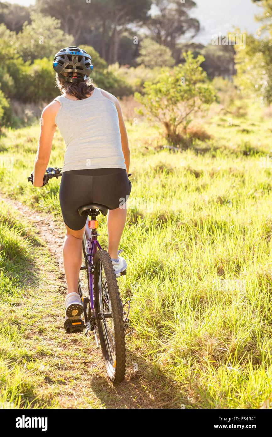 Rückansicht der sportliche Brünette Mountainbike Stockbild