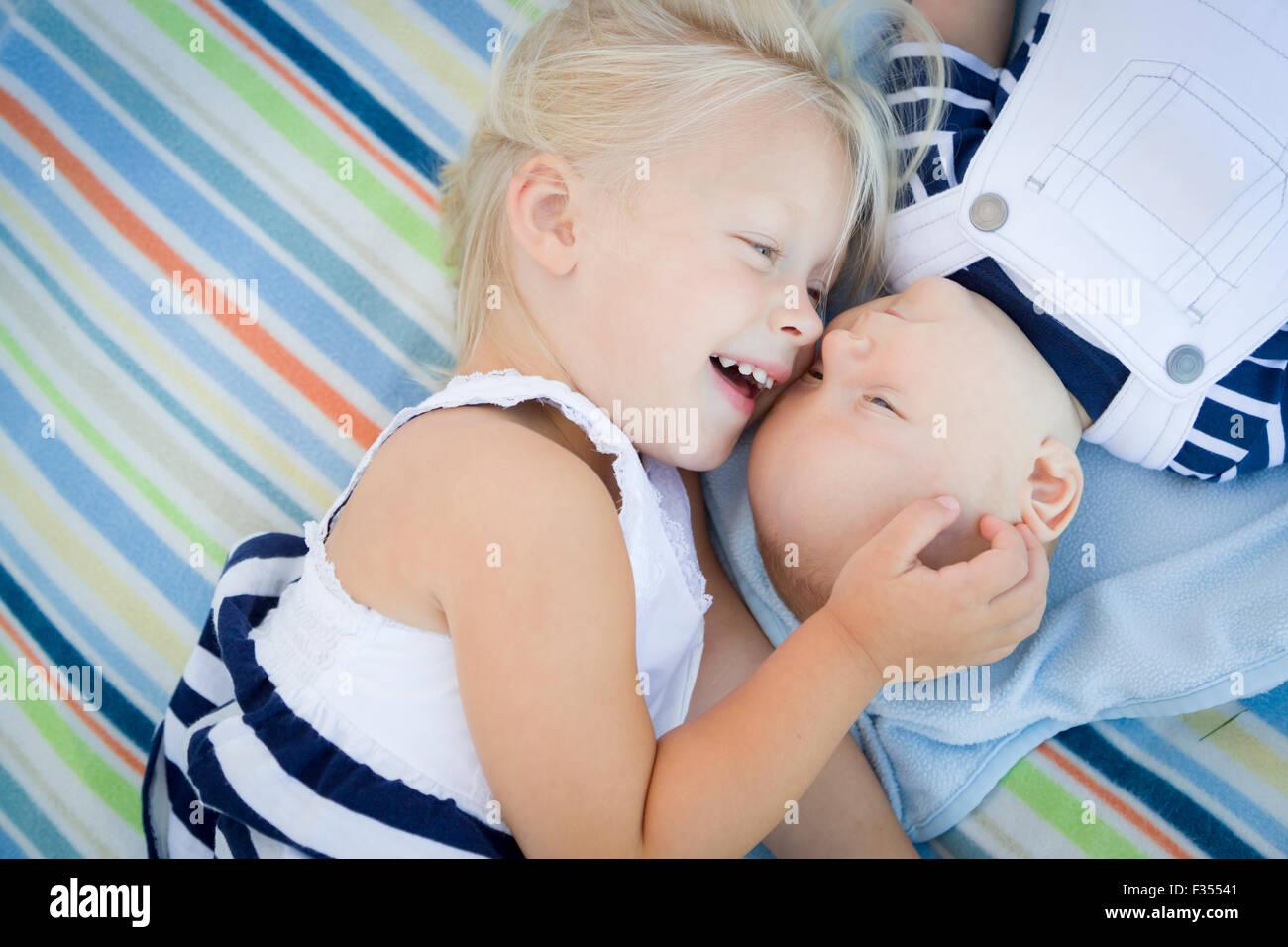 Niedliche kleine Schwester Verlegung als nächstes ihr Baby Bruder auf Decke. Stockbild