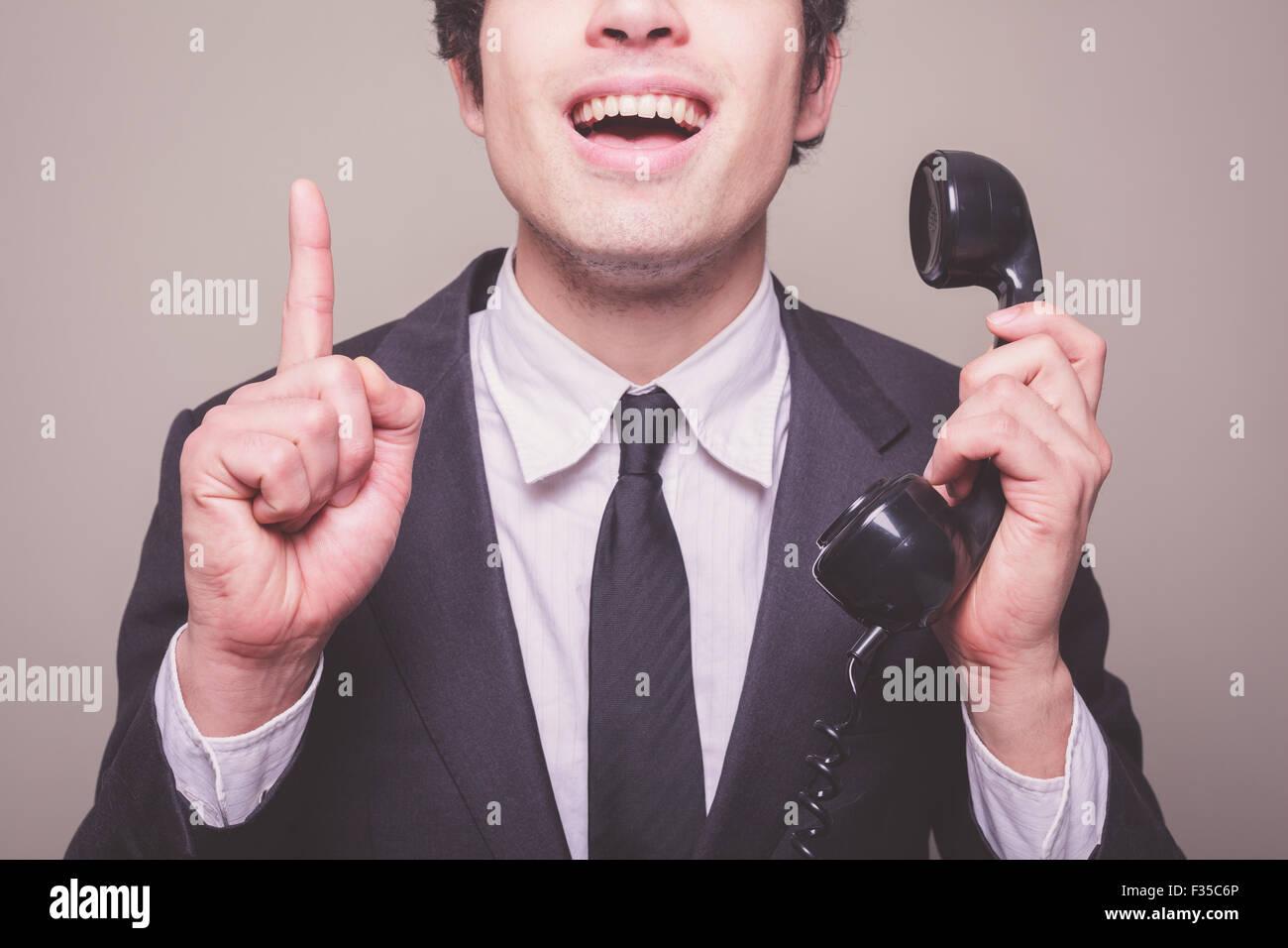 Junger Geschäftsmann auf dem Handy bekommt eine glänzende Idee Stockbild