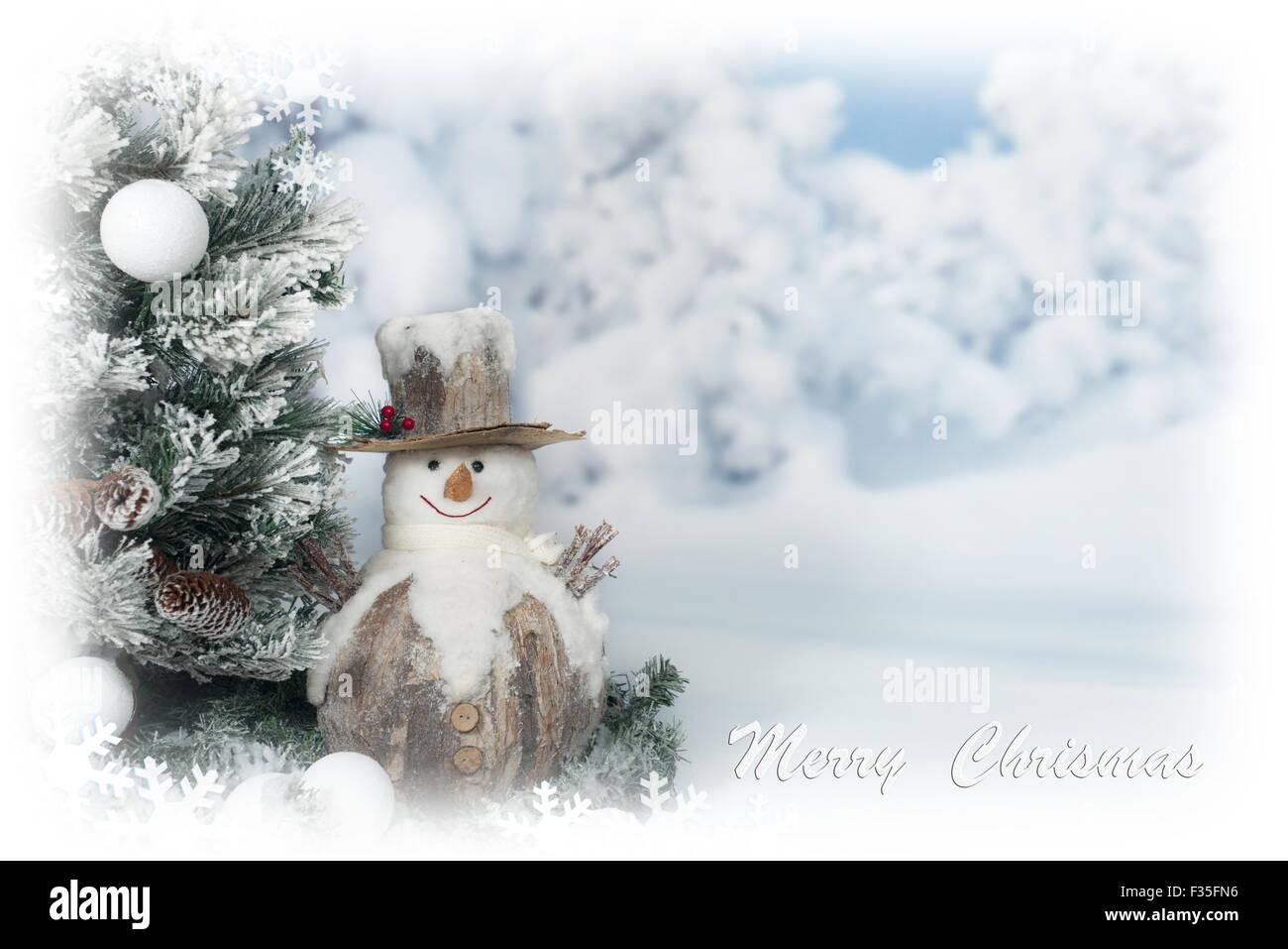 Frohe Weihnachten-Grußkarte mit Schneemann neben Baum Stockbild