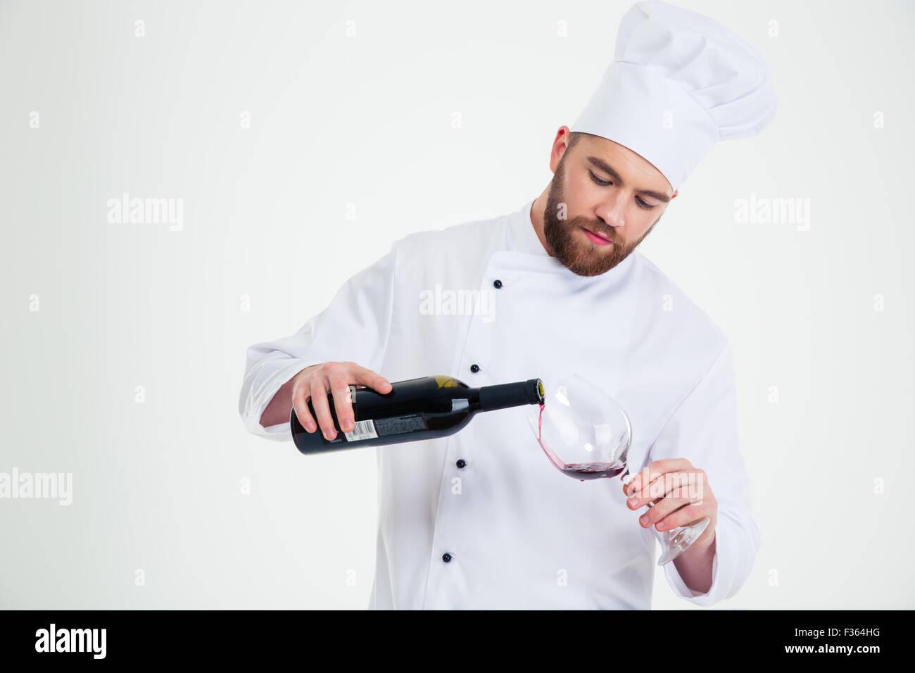 Porträt eines männlichen Küchenchefs Kochen gießt Wein im Weinglas isoliert auf weißem Stockbild