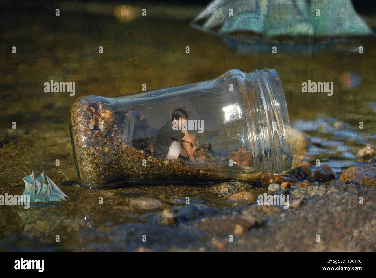 Junge in einer großen Flasche in Mitte des Wassers Stockbild