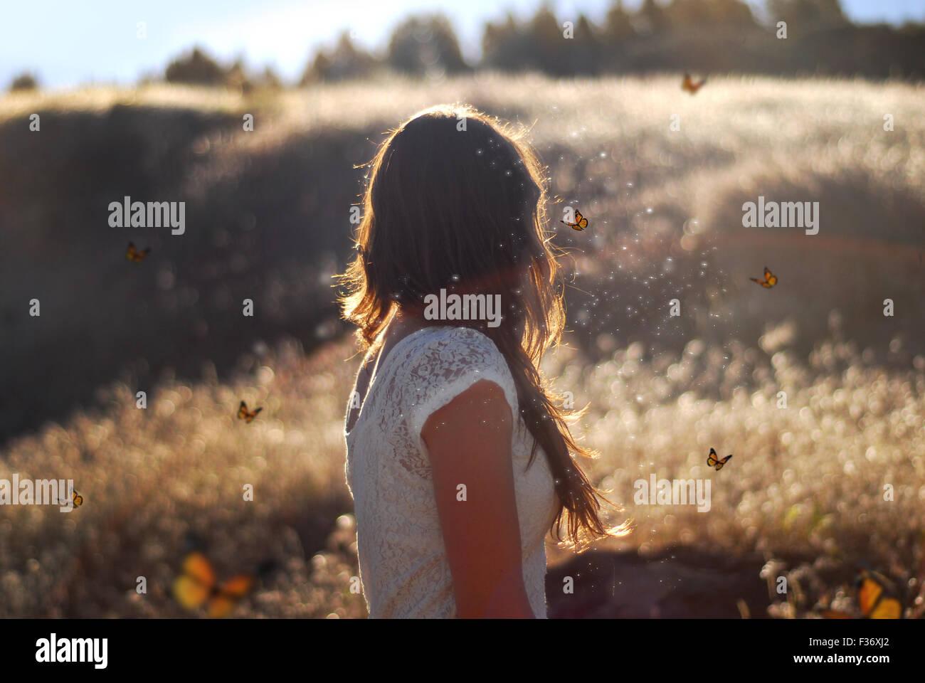 Mädchen in der goldenen Stunde im weißen Kleid mit Schmetterlingen fliegen um sie herum Stockbild