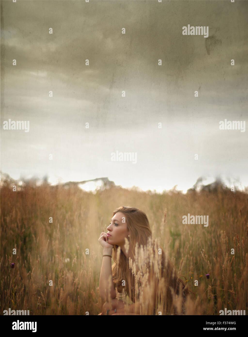 Mädchen sitzen zwischen Feldern mit einem stürmischen Himmel Stockfoto